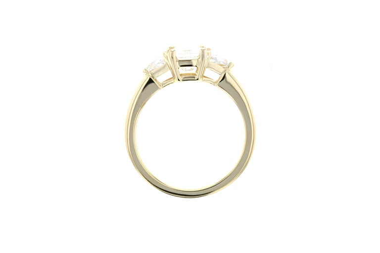 This engagement ring has a 1 carat center diamond and two diamond side trillions with a yellow gold setting and a gallery profile for a vintage look and feel.    Though this diamond ring is shown in yellow gold and with an emerald cut center stone,