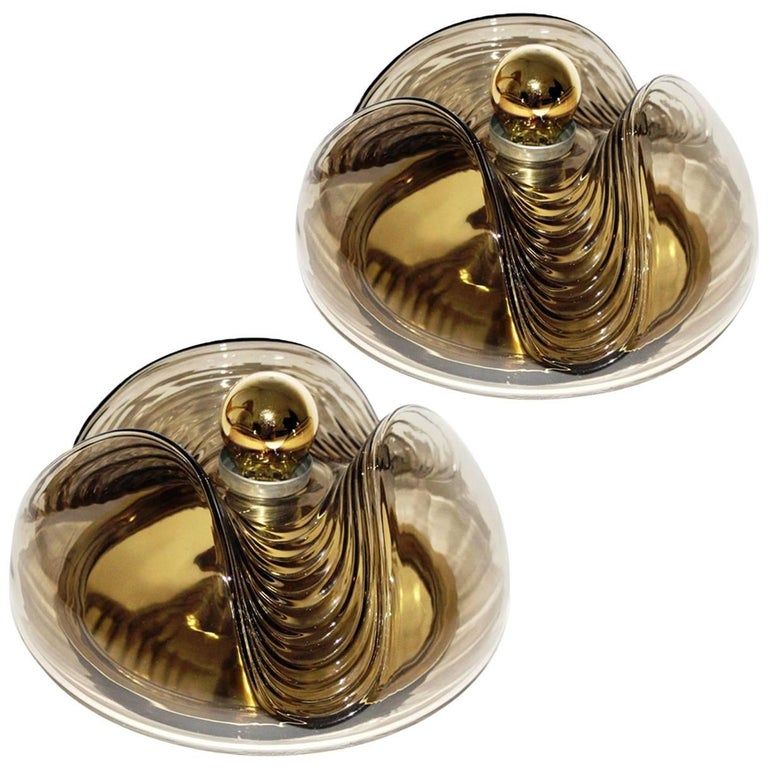 Exceptional flush mount or wall lights or sconces designed by Koch & Lowy for Peill & Putzler in the 1970s. Featuring a smoked glass globe shade with a waved or ribbed molded bubble form, casting a stunning rippled light across a wall or