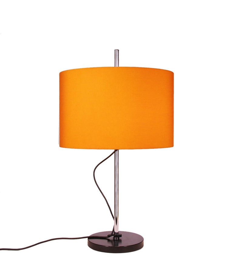 Set of two table lamps with chrome steel rod, black metal foot and the original orange adjustable lamp shade.    Measures: height: 15.75