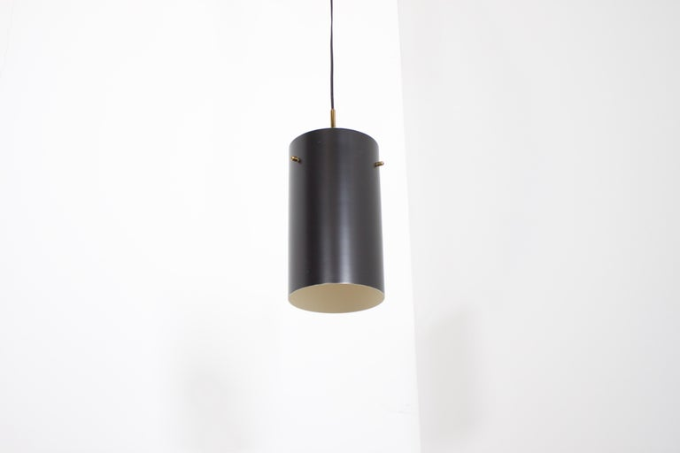 Minimalist Italian pendants in very good condition.  6 pieces available.   Manufactured by Stilnovo in the 1950s.   Executed in brass and black lacquered metal.  The cylindrical metal shade hangs on a frame with solid brass rods.  Original