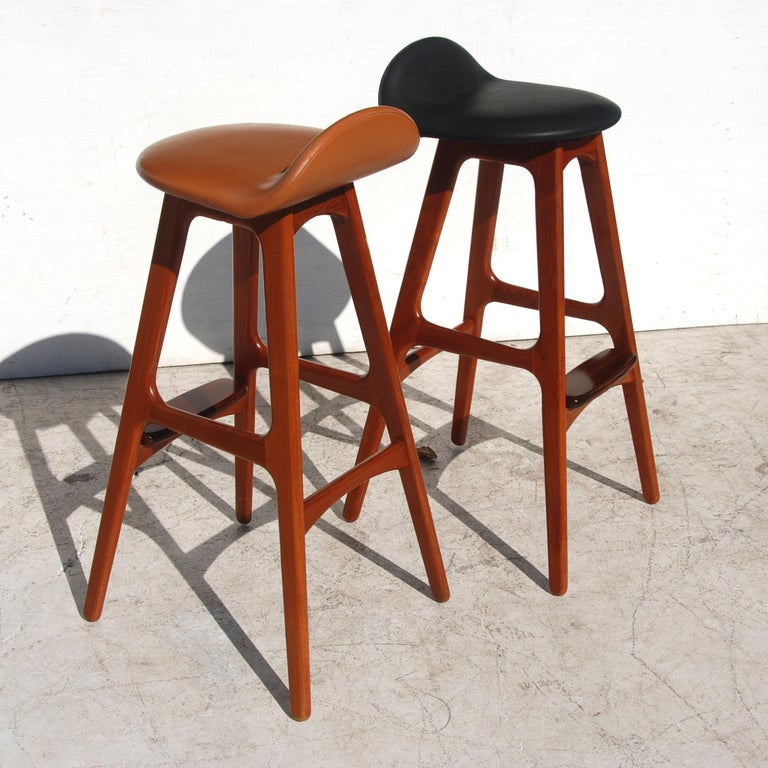 A Mid-Century Modern bar stool designed by Erik Buch and made by Oddense Maskinsnedkeri A-S. Teak frame with a rosewood footrest and leather upholstery.