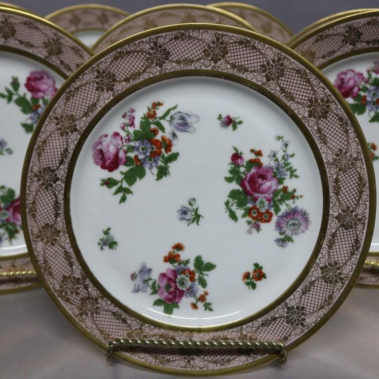 A set of 10 antique Bavarian porcelain dinner plates offer gilt lace and floral rims with wells having floral spray, en verso stamped