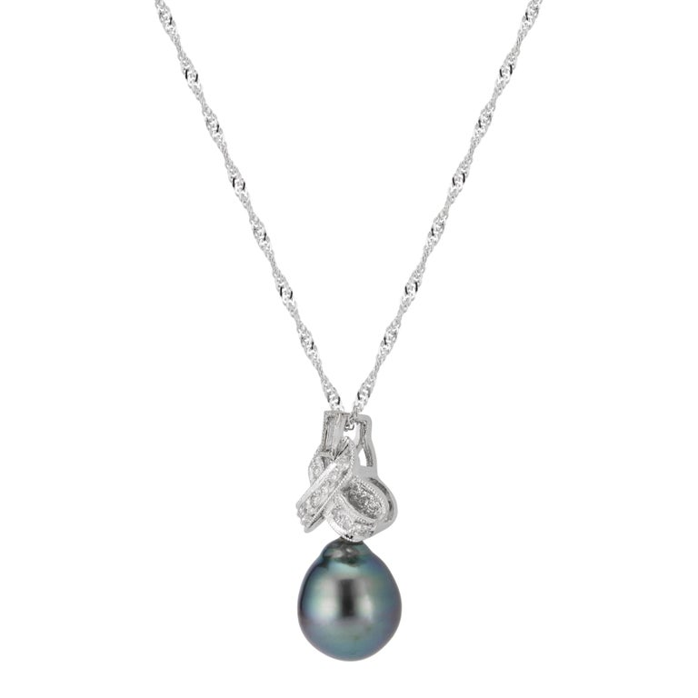 Black cultured south sea pearl and diamond necklace. Tear drop shaped black cultured South Sea pearl in a bow design 14 white gold pendant set with 16 round and 1 baguette diamond. 16 inches.   1 grey/black South Sea pearl, 9.3mm- 10.8mm 16 round