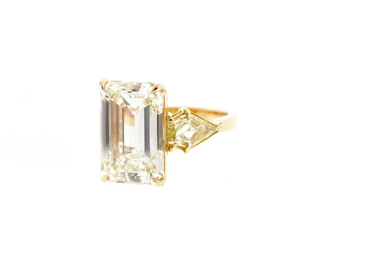 This vintage diamond ring features a 10 carat emerald cut center stone with a pair of fancy yellow kite cut side stones for a total carat weight of 11.37 and is set in two tone gold (rose and yellow) with delicate detailing under the basket.
