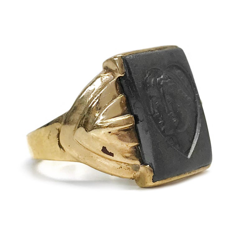 10 Karat Art Deco Hematite Intaglio Ring. The wide-band has an Art Deco motif and a smooth shiny finish. The center of the ring is a 15.86mm x 11.92mm Hematite Intaglio with a heart and a Roman couple. Stamped on the inside of the band is 10K. The