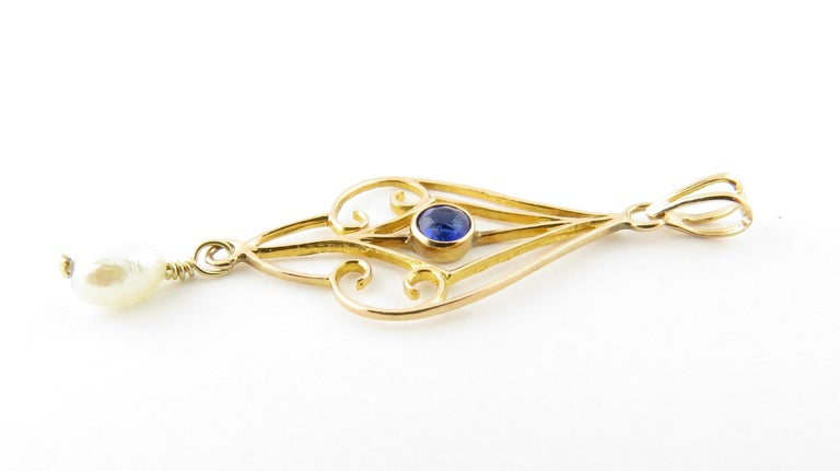 Vintage 10 Karat Yellow Gold Blue Sapphire and Pearl Pendant-  This lovely pendant features one round blue sapphire set in beautifully detailed 10K yellow gold and accented with one dangling freshwater pearl (5 mm).  Size: 27 mm x 13 mm  Weight: 0.4