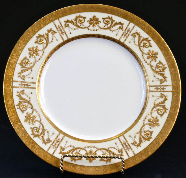 This elegant set of 19th century Minton, Stoke-on-Trent, England heavy raised paste 22-karat plates are for presentation or dinner. The plates have a white center with an ivory rim that is decorated with Adam-style beaded swags and scrolling