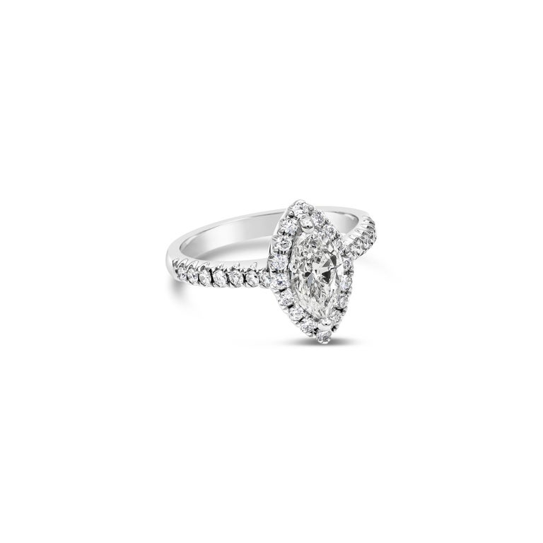 Showcasing a 1.00 carat marquise cut diamond, surrounded by a a single row of round brilliant diamonds. Set in a thin diamond encrusted shank made in 18 karat white gold. Accent diamonds weigh 0.41 carats total.   Style available in different price
