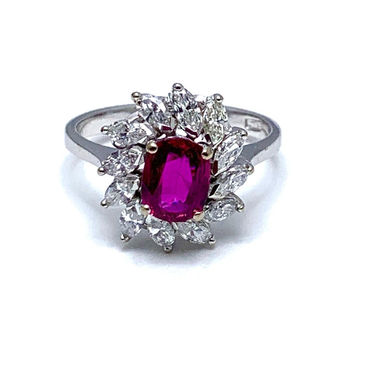 A vibrant currant red 1.00 carat Ruby and marquise Diamond engagement/cocktail ring in 14 karat white gold.  The Ruby is uniquely set slightly off center in conjunction with the slant set marquise Diamonds.  The 12 Diamonds have a total carat weight