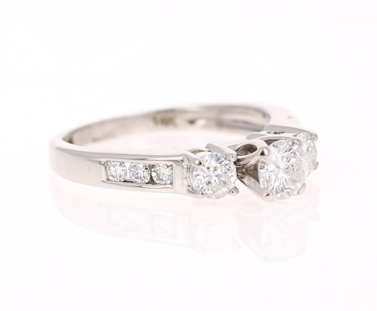 A classic 3-stone Diamond ring set in 14 Karat White Gold. A beautiful promise, engagement or wedding ring.   There are 9 Round Cut Diamonds that weigh 1.00 Carat. (SI-F)  It is set in 14K White Gold and weighs approximately 3.8 grams.   The ring is
