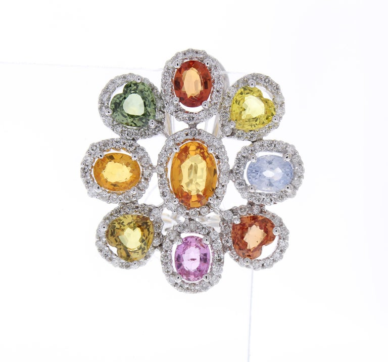 These are natural multi-colored sapphire cluster earrings that feature a bevy of colors coupled with contrasting white brilliant diamonds. 18 oval & heart shaped colorful sapphires total 10.00 carats. Round brilliant cut diamonds are prong set in