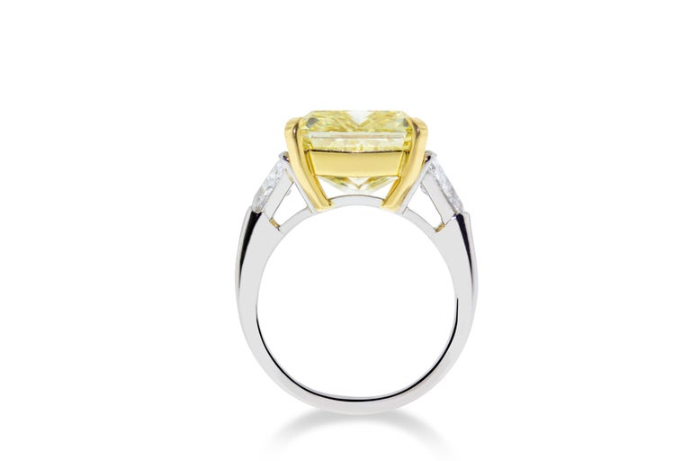 This 10.01 GIA certified VVS2 fancy yellow diamond is set in Platinum and 18K yellow gold. Flanked on either side by two F-G SI trilliant stones with a total weight of 1.21 carats. GIA Certified. Report No. 1186284205. Size 6 3/4. Made in Italy.
