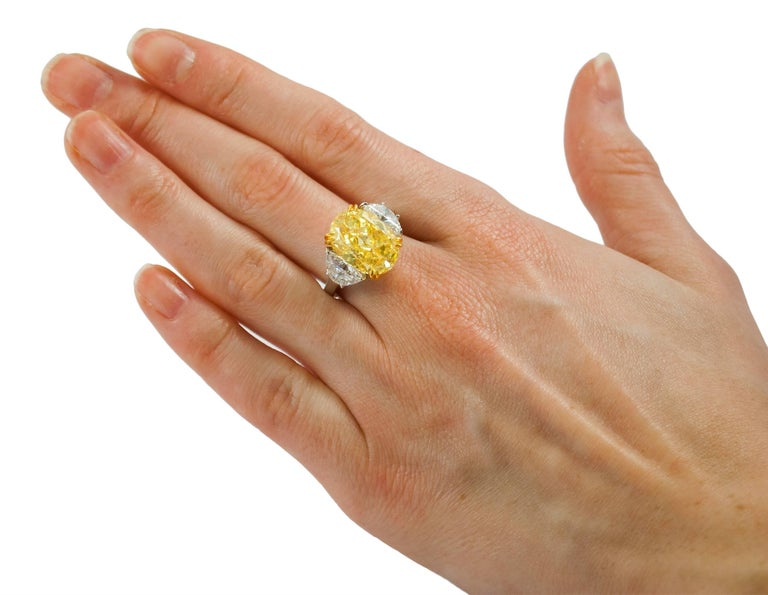 This captivating GIA certified 10.03 carat VS2 fancy yellow oval diamond,  is set in a platinum band with 18kt yellow gold prongs. Two half moons weighing 2.41 carats each, are set on either side of the center stone.  Purchase includes GIA report