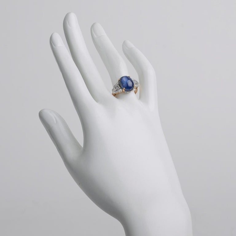 Dress ring, centering a fine cabochon-cut natural Burmese star sapphire weighing 10.18 carats, framed by baguette-cut and round-cut diamonds together weighing approximately 1.20 total carats, mounted in platinum and 18k yellow gold.
