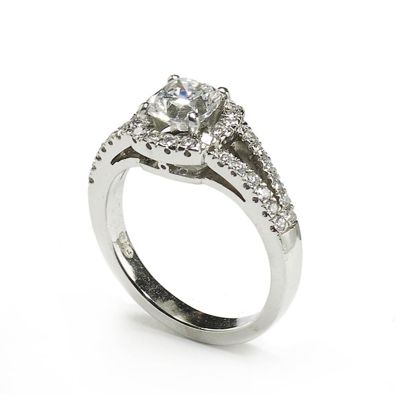 A diamond solitaire ring, set with a 1.01ct, D colour, S11 clarity, cushion brilliant-cut diamond, in a four claw setting, with a round brilliant-cut diamond surround and diamond set split shoulders, mounted in platinum, accompanied by a GIA