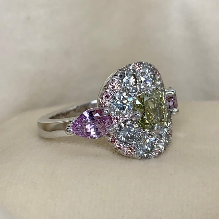 One of a kind ring in 18K White gold 10,2 g. Set with a fancy yellowish green diamond cushion centerstone 1,02 Carat, Fancy Grey diamonds 1,50ct., Fancy Pink diamonds 0,16 ct., fancy blue diamonds 0,08 ct., 2 pear shape unheated violet sapphires