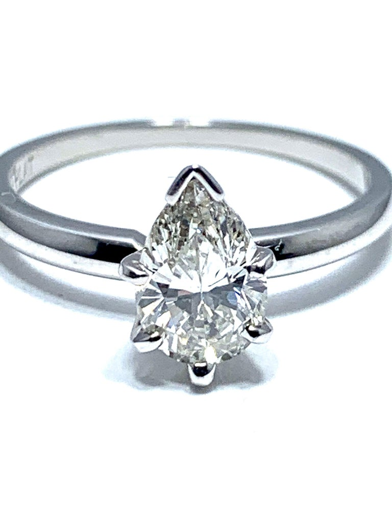 An eye catching 1.02 carat pear shape brilliant cut diamond engagement ring.  The center diamond is set in a six prong platinum head on a polished platinum shank.    The center diamond is graded by GIA as J color, VVS2 clarity, and displays a fury