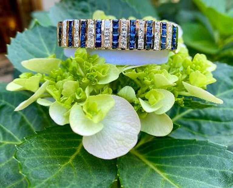 Sparkling diamond and sapphire 14 karat yellow gold estate hinged bangle bracelet features 17 rows of invisibly channel set princess cut white diamonds and square blue sapphires separated between 18 rows of vertical 14 karat gold sections. The total