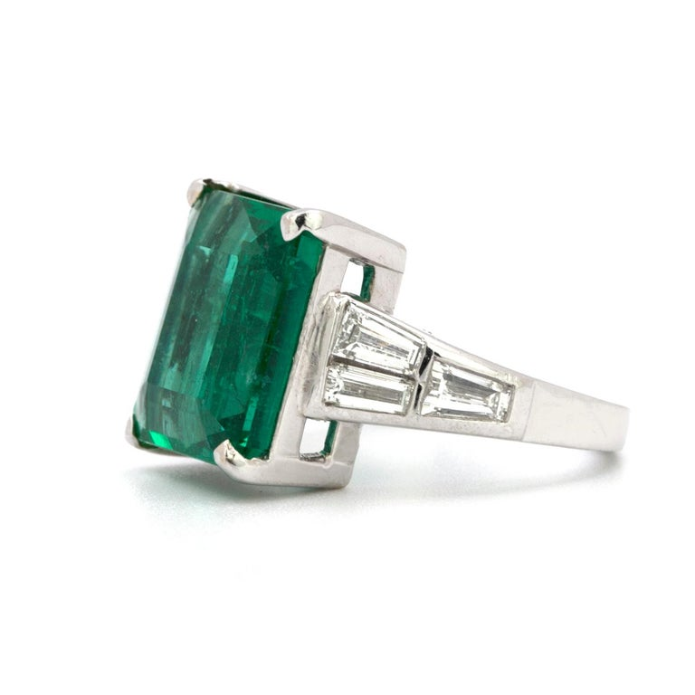 A beautifully crafted platinum ring that features a 10.23 carat Colombian colored natural emerald is set with 6 clean white tapered baguette diamonds that weigh in total 1.50 carats.    Size 6 1/4