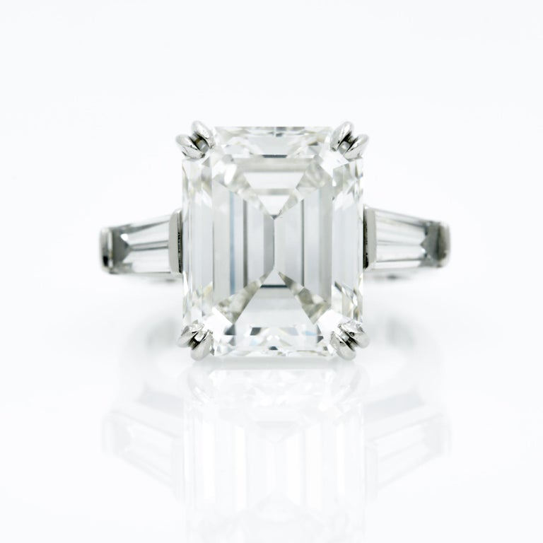 Weighing 10.27 carats, the center emerald cut diamond of this three stone diamond platinum ring is eye catching. The diamond is GIA certified with H coloring and VS clarity. It is bordered by two tapered baguette diamonds weighing 1.15 carats