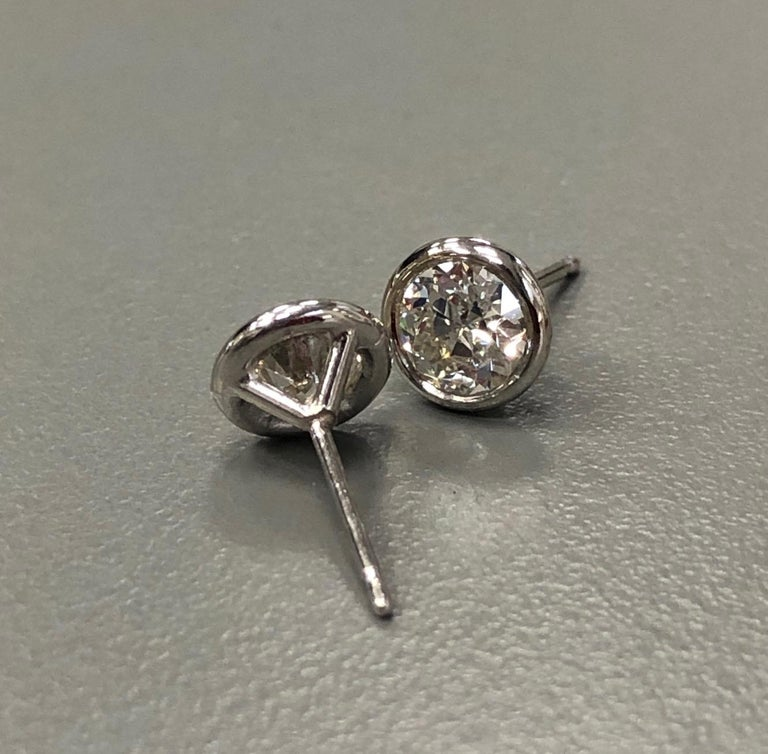 The 14 Karat white gold bezel set diamond stud earrings, weighing 1.04 carat in total, are centered on 2 transitional circular cut diamonds H-I Color SI2-VS2 Clarity. Evoking a vintage look, these are truly stunning.