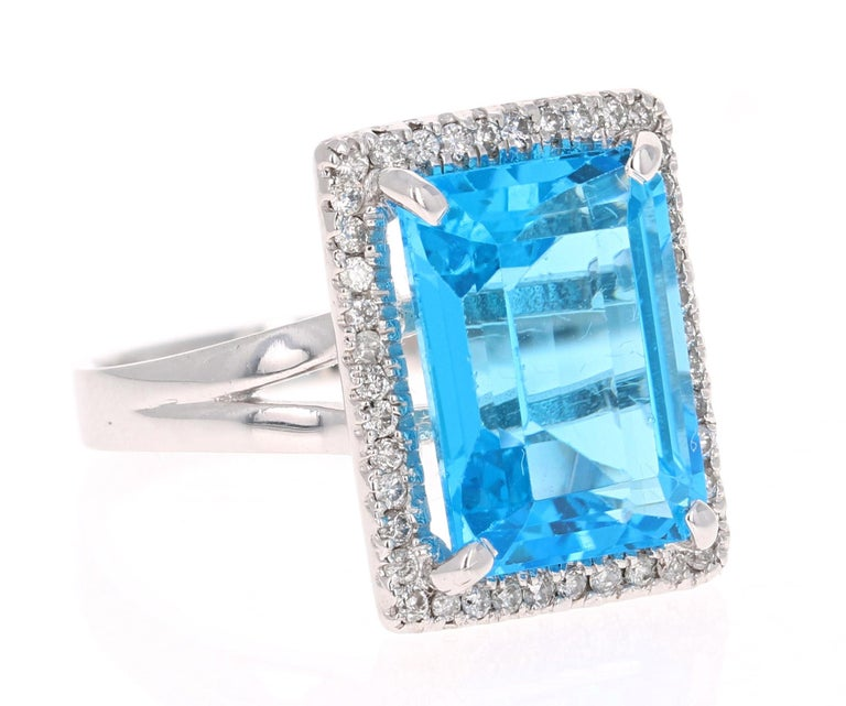 This stunning statement ring has a large Emerald Cut Blue Topaz that weighs 10.21 Carats.  It is surrounded by a simple halo of 43 Round Cut Diamonds that weigh 0.38 Carats.   It is crafted in 14 Karat White Gold and weighs approximately 5.5 grams.