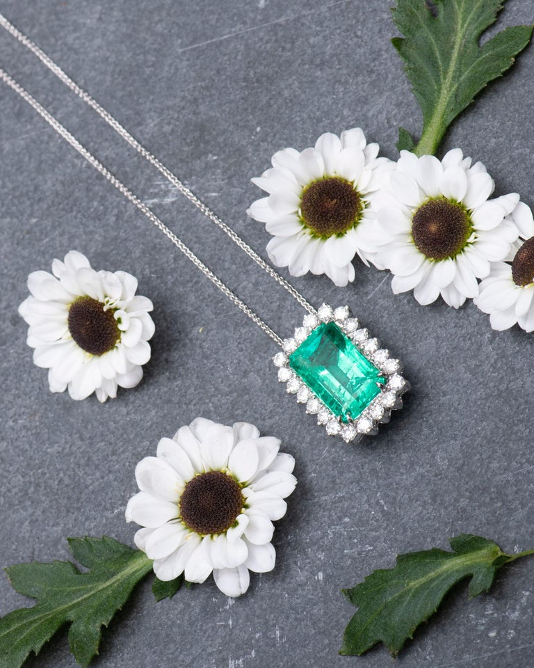 14K white gold pendant set with one 10.60 carat weight emerald cut Colombian emerald with 1.50 carats total weight in round diamonds.