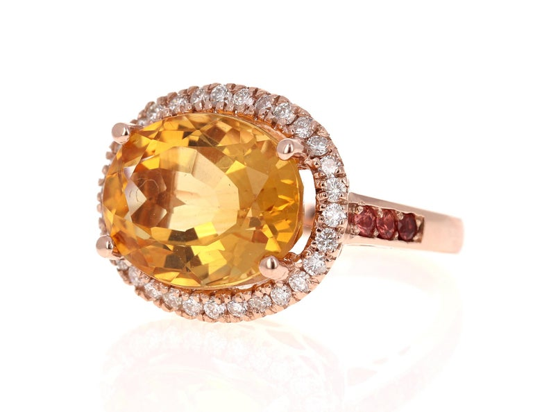 A Stunning and uniquely designed beauty to say the least!   This magnificent ring has a bold Oval Cut Citrine that is blazing yellow! It weighs 9.90 Carats and is surrounded by a beautiful halo of 30 Round Cut Diamonds that weigh 0.56 Carats.