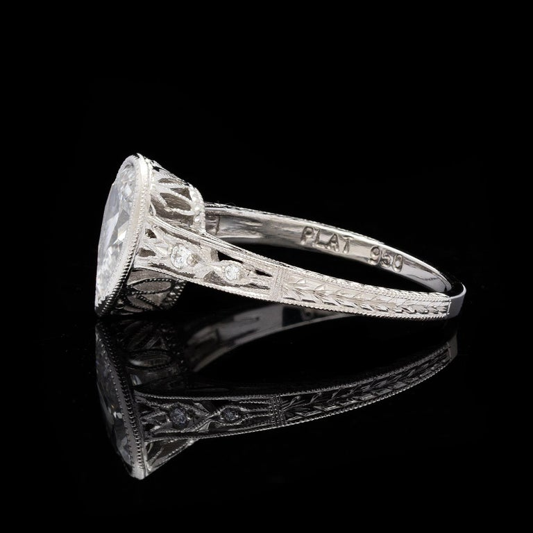 Pretty platinum filigree ring features a 1.08 carat pear shape brilliant cut diamond (approximately K/SI2) accented with 4 round brilliant cut diamonds.  Ring size is a 6.25 and can be resized.  Fine craftsmanship of engraved scroll-work & milgrain
