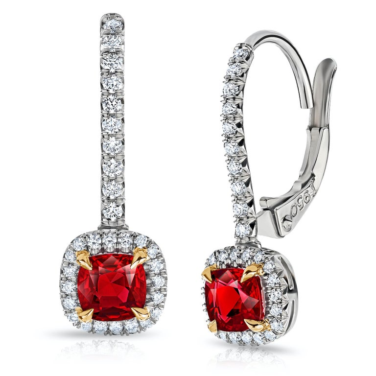 Ruby and diamond halo earrings with a total Ruby weight of 1.09 carats and total diamond weight of 0.24 carats set on platinum and 18k yellow gold lever backs