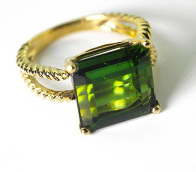Beautiful emerald cut glittering green 10.96 Carat Tourmaline set in a 14 KT yellow gold ring size 7.5 (sizable).  The gemstone measures approximately 12 mm x 11 mm.  There are no eye visible inclusions in the gemstone.