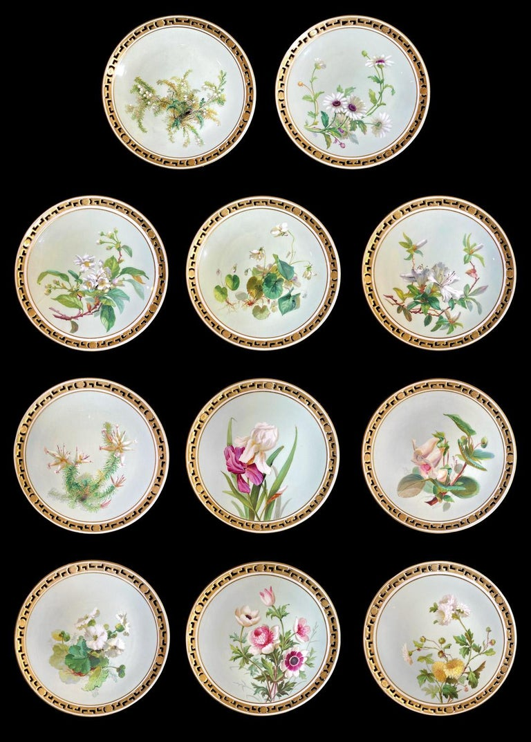 Set of 11 dinner plates in Minton Porcelain. Each plate is decorated with and hand painted flower on a green-blue background framed by a gold filet. The edge of the plate is openwork with a greek style pattern alternated with some small flowers and