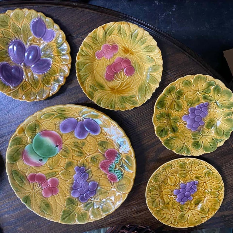 Set of Sarreguemines French Faience Majolica dessert plates, with a variety of fruit on a background of overlapping leaves.  Glazed by hand, each plate stamped  2 strawberry, 1 plum, 1 cherry, 2 grape, 2 pears and 2 apples  1 serving platter