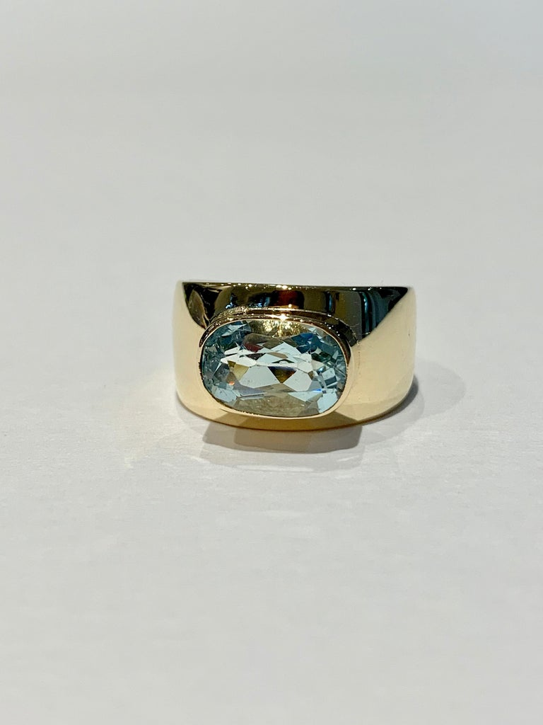 The pretty pale blue oval Aquamarine* sits in a very contemporary 9ct Yellow gold band.  The stone has amazing clarity and is set in an east to west design.  The Aquamarine measures 11 x 7 x 5.5 mm,  approximately 3ct.  Please be aware that the