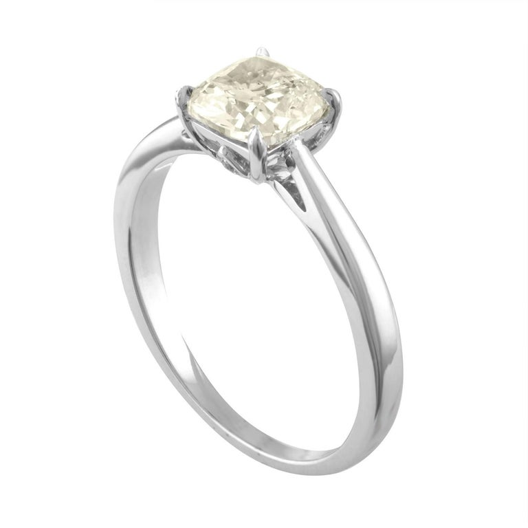 Solitaire Engagement Ring The ring is 18K White Gold The center is a Cushion Cut Stone 1.10 Carats K VS2 There are 2 small diamonds on the crown 0.02 Carats G VS The ring is a size 6, sizable. The ring weighs 2.6 grams