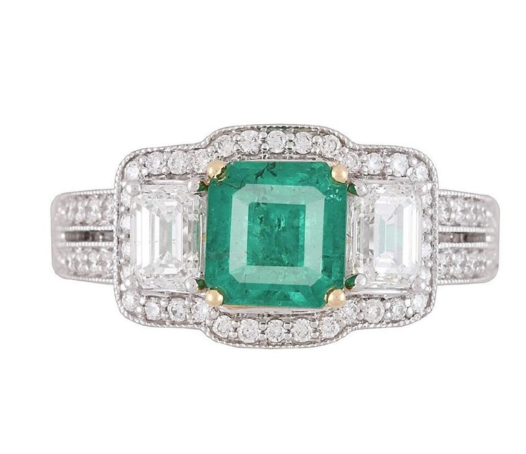 This gorgeous ring carries a 1.10 carat cushion cut Emerald center, flanked by baguette diamonds and surrounded by round white diamonds. Additional round diamonds trace down the split shank, bringing the total diamond weight to 1.03 carats.