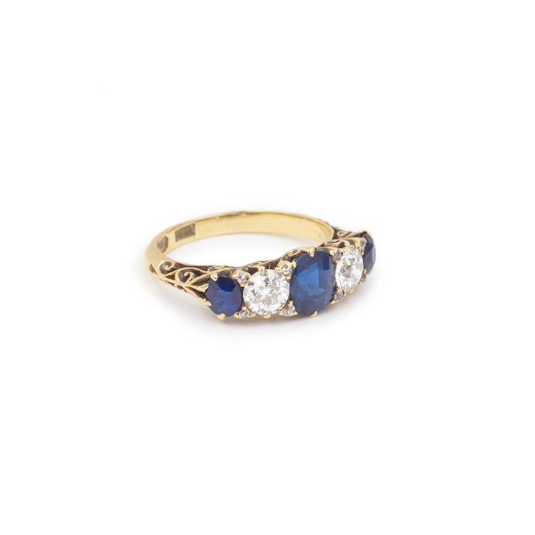 Jarretière ring set in the center of a cushion sapphire of about 0.85 carats.  The central stone is surrounded by two old cut diamonds and two oval cut sapphires.  Diamond weight: approx 0.70 carats  Weight of the two oval sapphires: approx 0.26