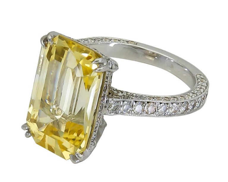 A magnificent engagement ring showcasing a long emerald cut yellow sapphire, set in a diamond encrusted basket and shank. Made in platinum. Yellow Sapphire weighs 11.06 carats.  Size 6 US (sizable) Dimensions: 0.62 in x 0.42 in.
