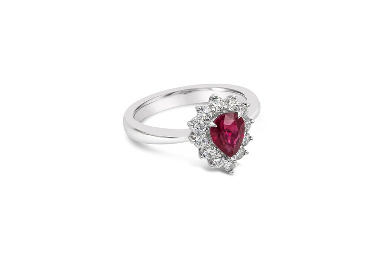 A beautiful and unique engagement ring style showcasing a 1.11 carat color-rich pear shape ruby, set in a brilliant diamond halo in 18k white gold. Diamonds weigh 0.46 carats total. Size 6.5  Style available in different price ranges. Prices are