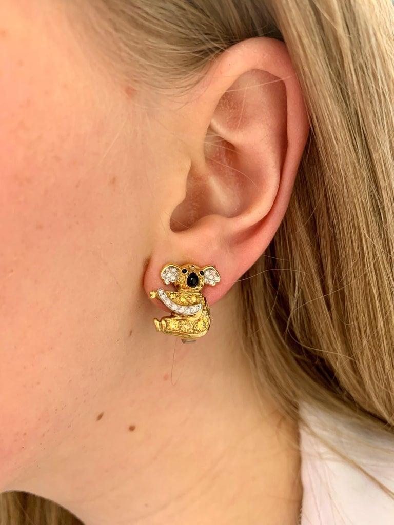 Fancy Intense and Vivid Yellow diamonds, 0.70ct Round brilliant diamonds, 0.42ct, F/G, VS  An adorable pair of vintage koala bear diamond, yellow diamond and onyx stud earrings in 18-karat yellow and white gold, circa 1980. Each earring modelled as