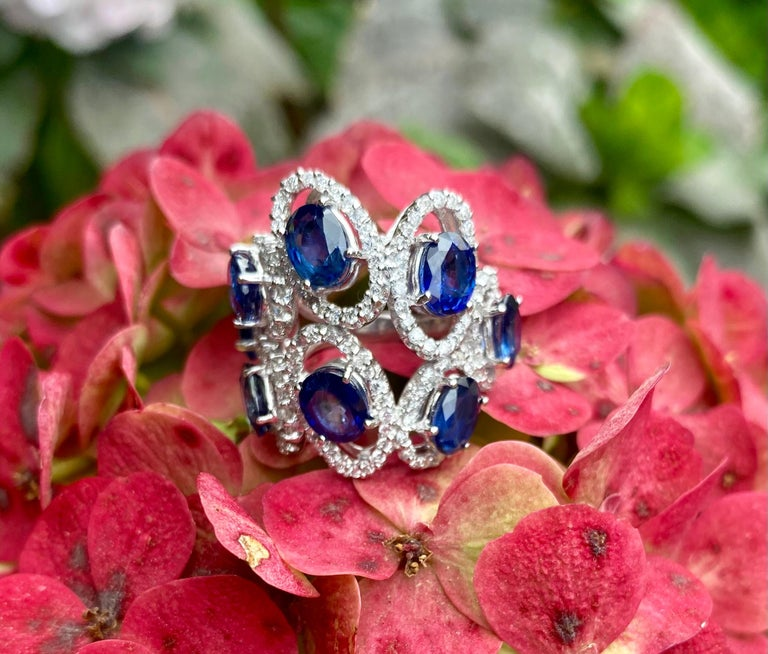 Exquisite and very striking, 18 karat white gold estate sapphire and diamond cocktail ring features 8 oval shaped full cut faceted natural blue sapphires, each suspended in a diamond halo, giving them a dreamy floating like affect.  Each blue