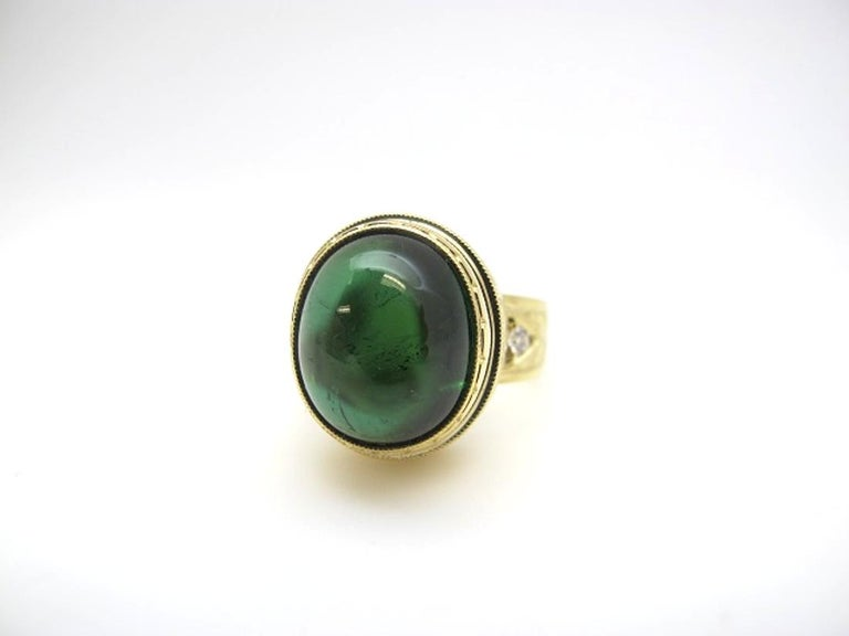 This stunning ring features a beautiful 11.28 carat tourmaline cabochon of saturated, pine-green color. The tourmaline is translucent with excellent clarity. Two brilliant cut diamonds add sparkle to the intricately engraved band. Handmade  in 18k