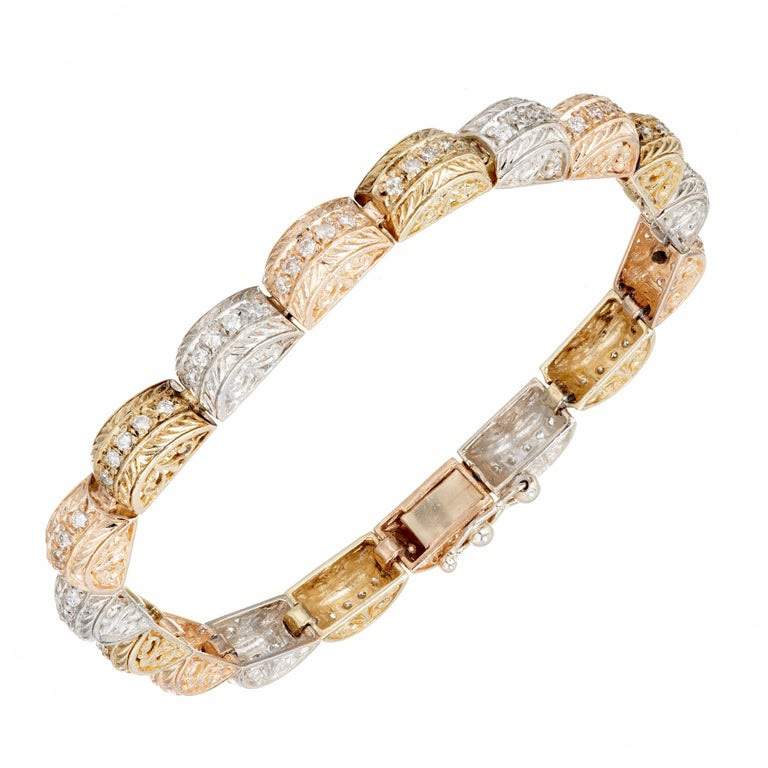 Hinged domed link bracelet with pierced sides and engraved tops. Tri-color 14k yellow, Rose and white gold.   89 full cut diamonds, approx. total weight 1.15cts, F, VS2 to SI1  Length: 7 inches  Width: 5.46mm  Height: 5.2mm  Hand engraved and bead