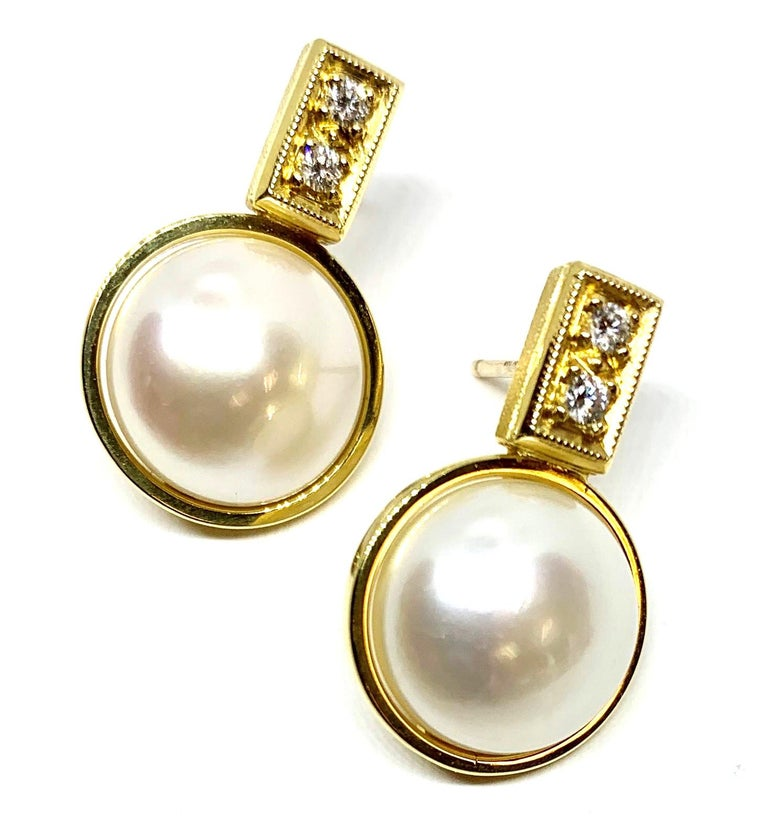Two giant button pearls, each measuring 11.5 millimeters in diameter are featured in these beautiful earrings.They are large and lustrous!  Sparkly diamonds are set at the top of the earrings; they weigh a total of .22 carats. We designed these