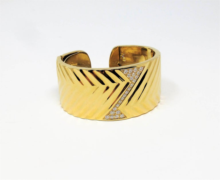 Bold, contemporary statement piece that absolutely shines on the wrist. This incredible cuff bracelet has a distinctive textured zig-zag pattern throughout, as well as a glittering pave diamond design at the center. The sleek lines and modern design