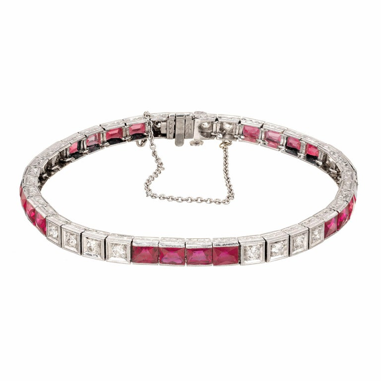 Ruby and diamond handmade hinged square link bracelet. 1940's with engraved sides. Hidden built in catch and underside safety. Calibre cut natural Rubies simple heat with minor residue. Round full cut diamonds.    20 calibre Emerald cut bright red
