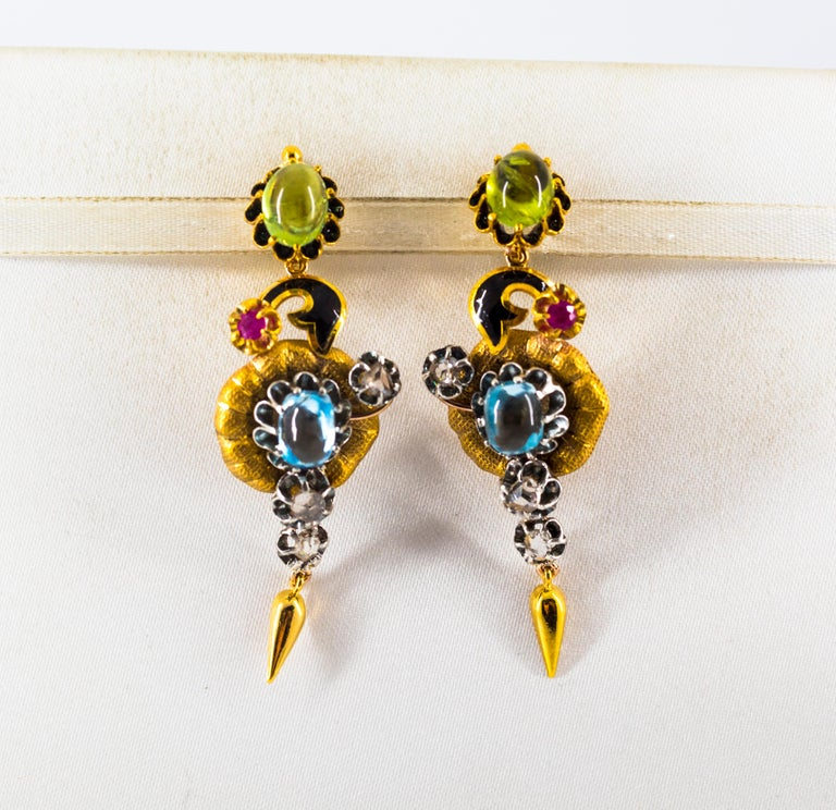 These Lever-Back Earrings are made of 9K Yellow Gold and Sterling Silver. These Earrings have 0.80 Carats of White Rose Cut Diamonds. These Earrings have 0.30 Carats of Rubies. These Earrings have 5.50 Carats of Blue Topaz. These Earrings have 5.00