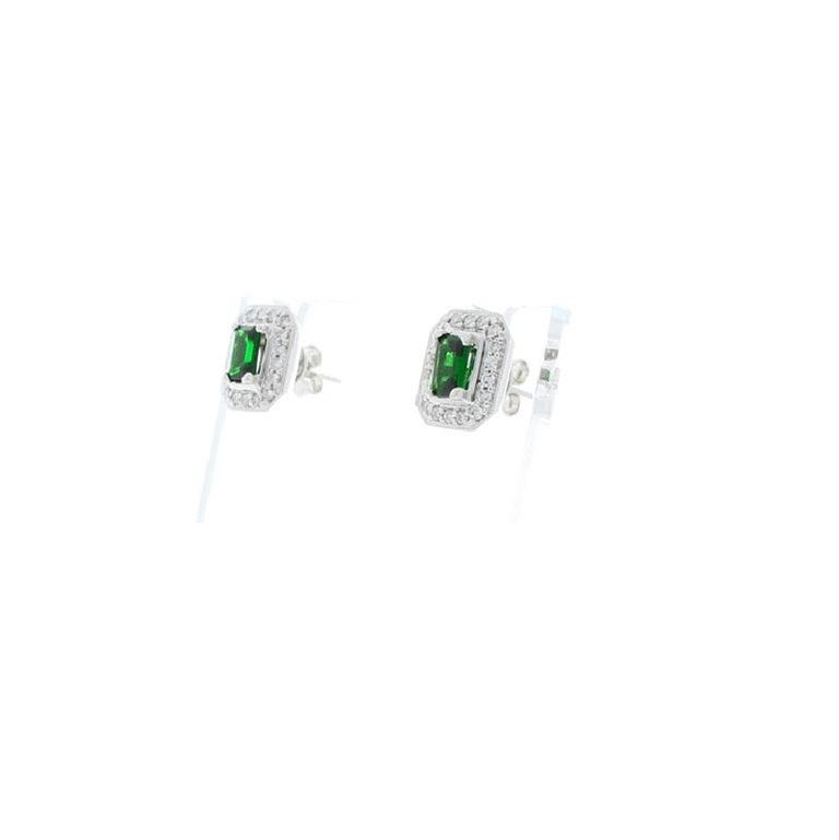 A splash of deep green adds an exotic accent to any ensemble. These unique studs showcase an emerald-cut Tsavorite garnet at the center of each earring, surrounded by a bright, brilliant halo of exceptionally sparkling white diamonds. The combined