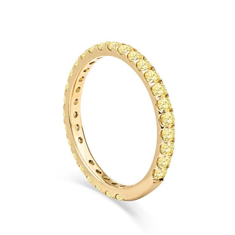 This unique stacking band features 32 round yellow natural sapphires that have a total weight of 1.18 carats and are set with split prongs in 14kt yellow gold. The ring is approximately 2mm wide and is a size 6 with some sizing space. It is a