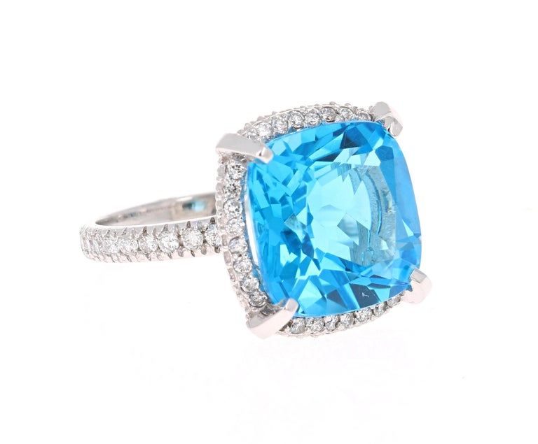 Stunning Cushion cut Blue Topaz and Diamond ring has a gorgeous large Blue Topaz that weighs 11.33 Carats. It is surrounded by 50 Round Cut Diamonds that weigh 0.59 Carats. The total carat weight of the ring is 11.92 Carats.  The ring is crafted in